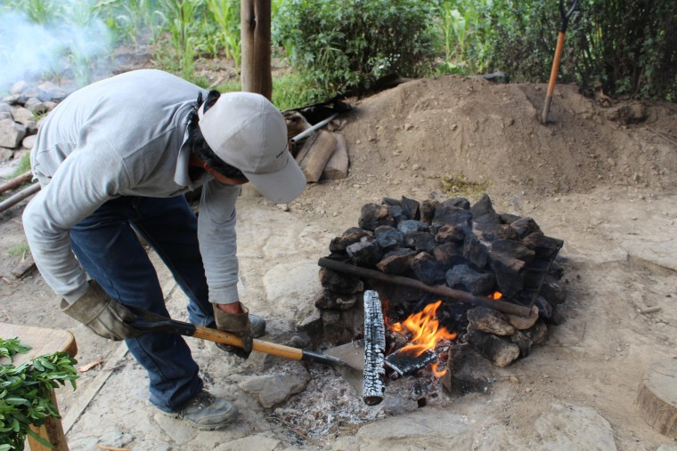A man removes the burning firewood now that stones are hot enough for food prepared the 'pachamanca' way.