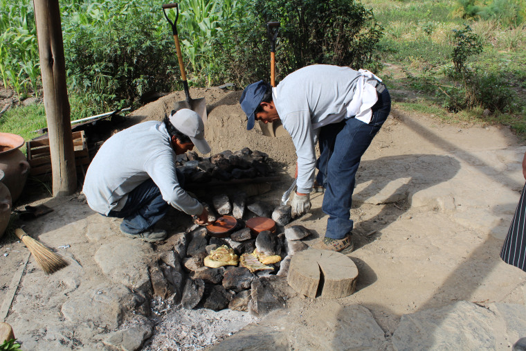 Putting more hot stones on top of the raw meat as Peruvians prepare 'pachamanca.'