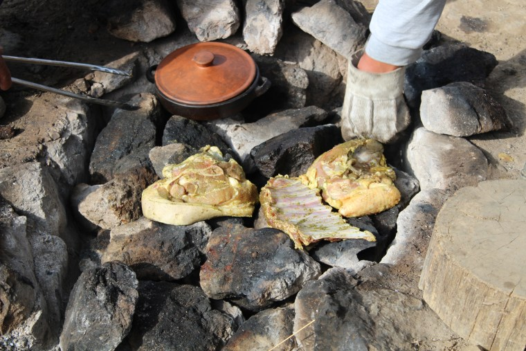 Placing the meat on the hot stones is part of the way to prepare 'pachamanca.'