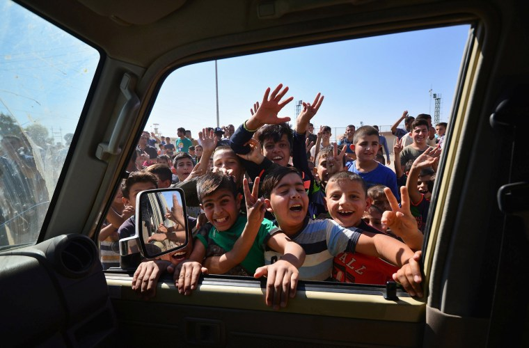 Image: Iraqi boys gather on the road as they welcome Iraqi security forces members, who continue to advance in military vehicles in Kirkuk