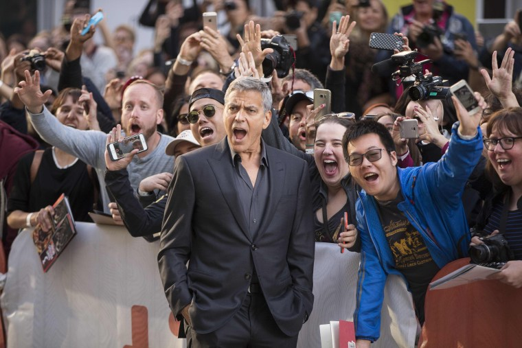 Image: George Clooney poses with fans at a film premiere