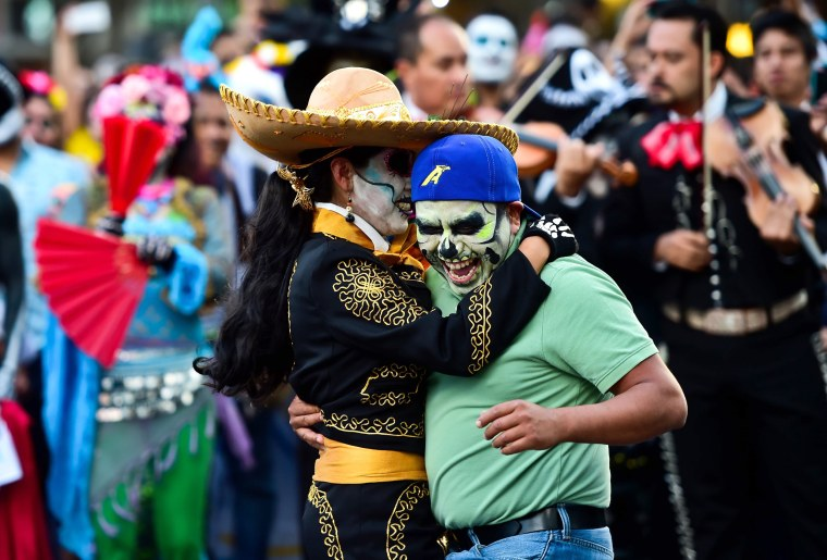 Image: A couple dances during the parade as other participants watch.