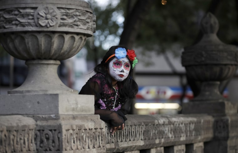 Image: A girl leans against stone benches as she awaits the start of the Grand Procession.