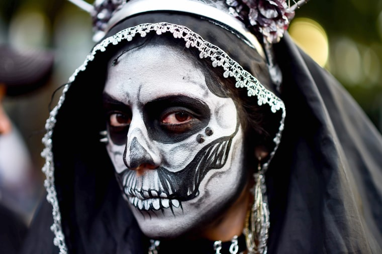Image: A woman wears traditional face paint representing death.