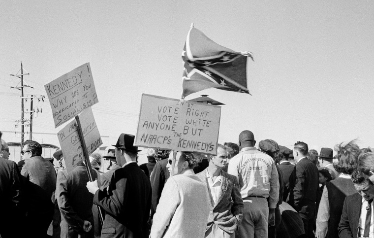 Image: People, including right-wing protesters carrying a Confederate flag and anti-Kennedy placards, await the arrival of President Kennedy