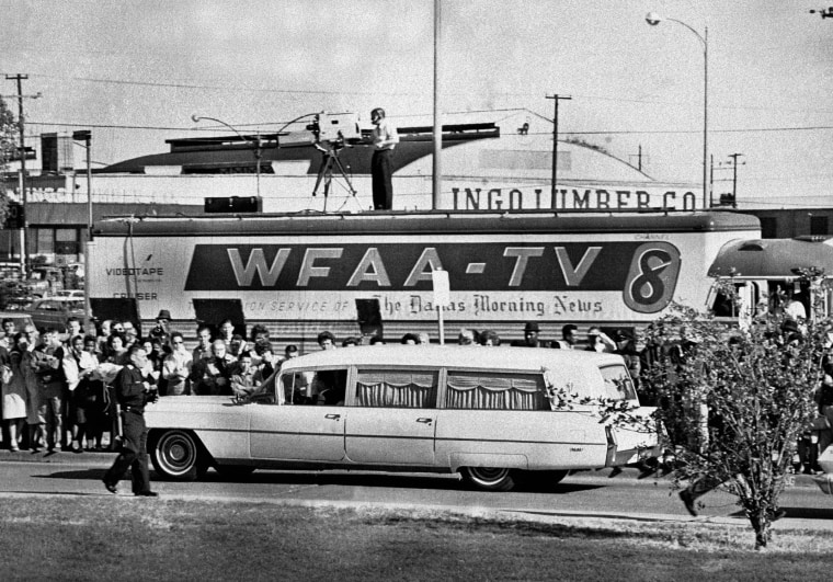 Image: People line the street as the hearse bearing the body of slain U.S. President John F. Kennedy drives past a television truck as it leaves Parkland Hospital