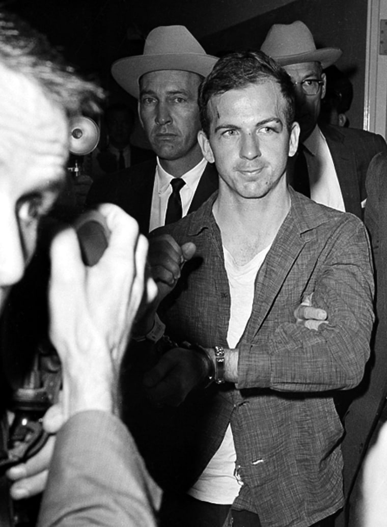 Image: Lee Harvey Oswald, suspected assassin of U.S. President John F. Kennedy, holds up his manacled hands at police headquarters in Dallas