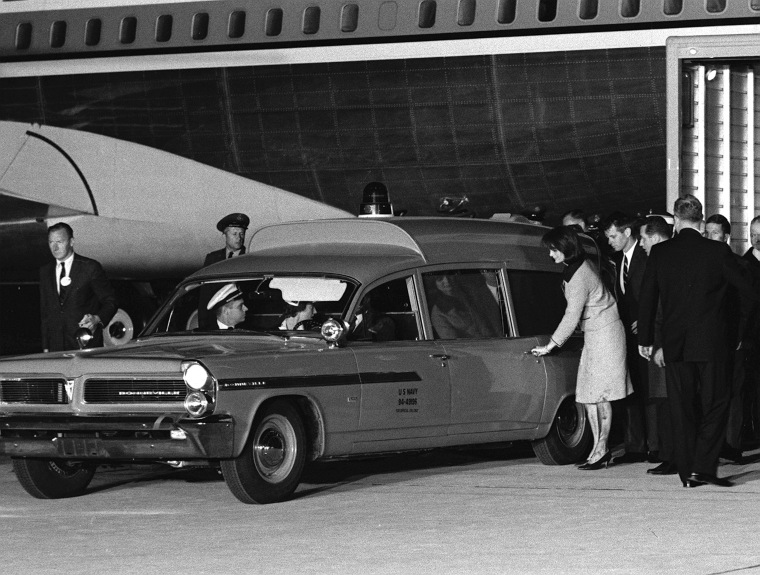 Image: Her stockings and dress soiled, widowed first lady Jacqueline Kennedy reaches for the door of the ambulance carrying the body of her slain husband at Andrews Air Force Base