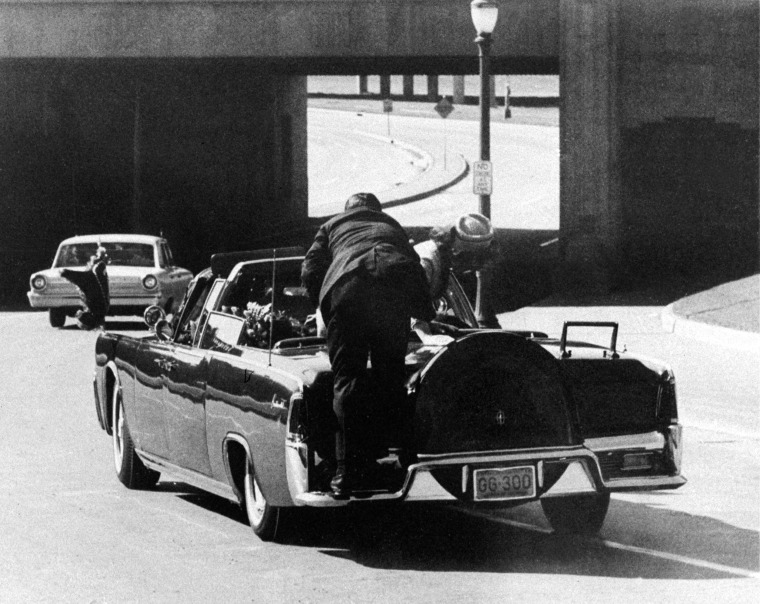Image: President John F. Kennedy slumps down in the back seat of the Presidential limousine as it speeds along Elm Street toward the Stemmons Freeway overpass