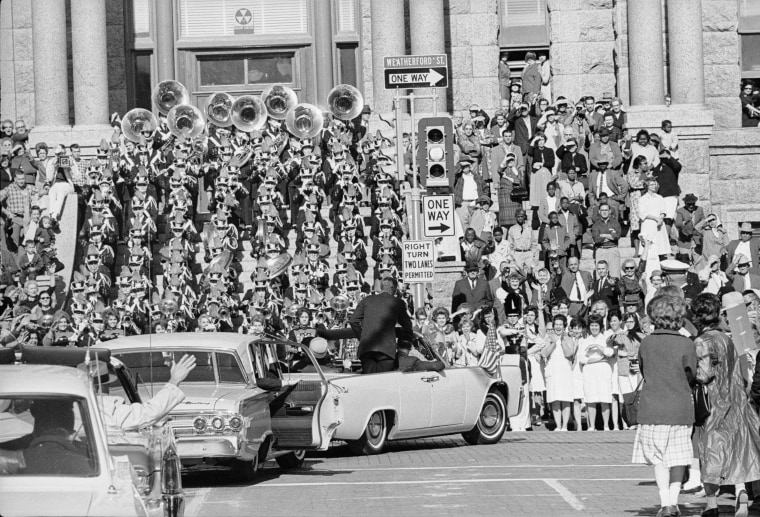 Image:  President John F Kennedy stands in his motorcade as it passes a brass band and viewing stand, and turns onto Weatherford Street in Fort Worth