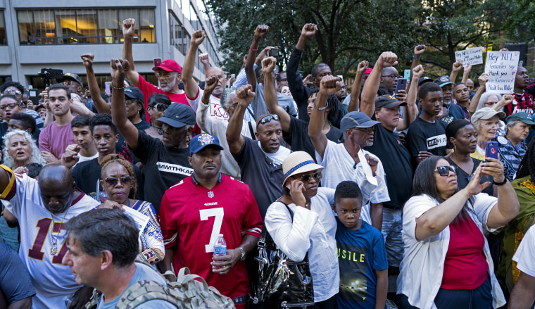 People raise their arms as hey gather in support of unsigned NFL quarterback Colin Kaepernick on Wednesday, Aug 23, 2017, in front of NFL headquarters in New York.