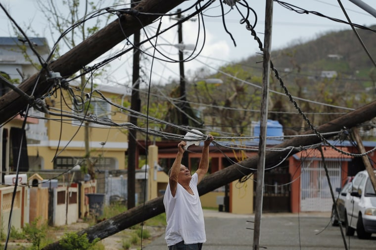 Image: A resident uses a plastic bag to move downed power cables so he can drive underneath them in a neighborhood that has not seen recovery efforts following Hurricane Maria in Ceiba