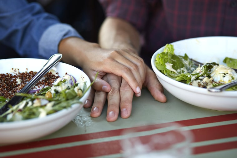 Image: Close-up of couple holding hands at lunch