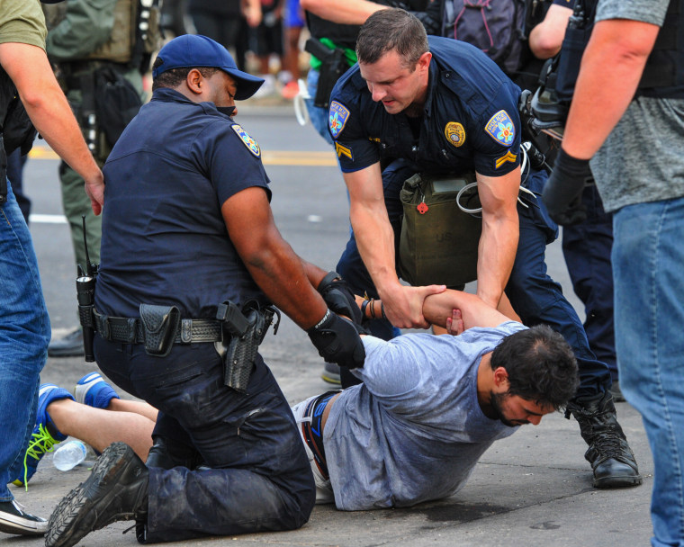 Police officers detain a protester as they try to clear streets while protesters were gathering against another group of protesters in Baton Rouge, La., Sunday, July 10, 2016.