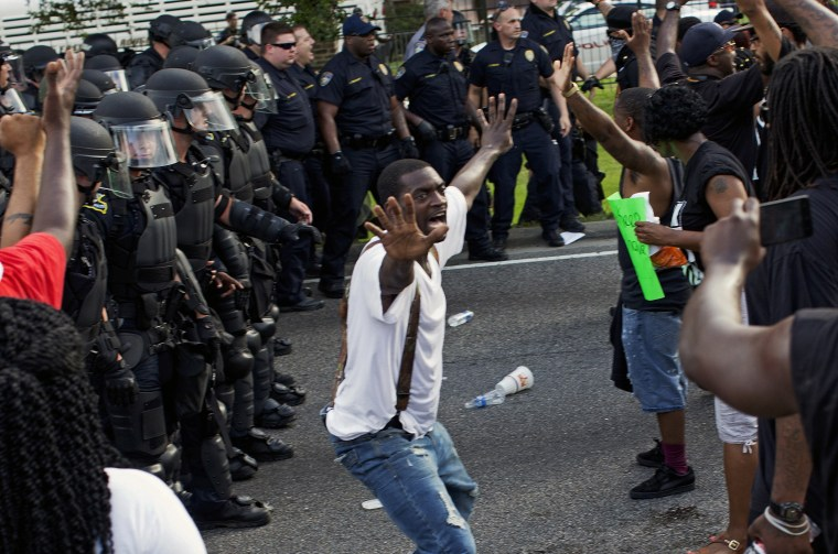 A man attempts to stop protesters from engaging with police in riot gear in front of the Police Department headquarters in Baton Rouge, La., after police attempted to clear the street on July 9, 2016.