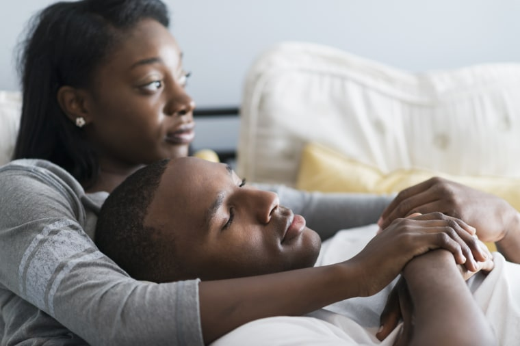 image: Young black couple lying in bed