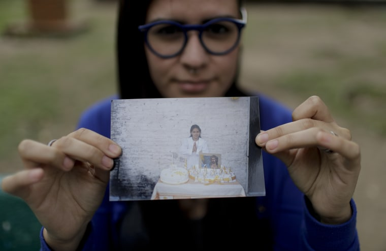 Karen Maydana, 22, shows a picture of herself as a child celebrating her first Holy Communion in Caseros, in the province of Buenos Aires, Argentina.