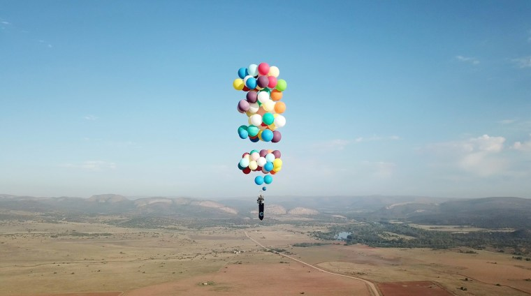 Image: Tom Morgan, from Bristol-based company The Adventurists, flies in a chair with large party balloons tied to it near Johannesburg, South Africa