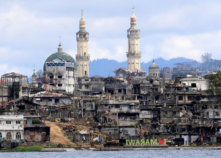 """Image: A signage of \""""I love Marawi\"""" is seen in front of damaged houses, buildings and a mosque inside a war-torn Marawi city"""
