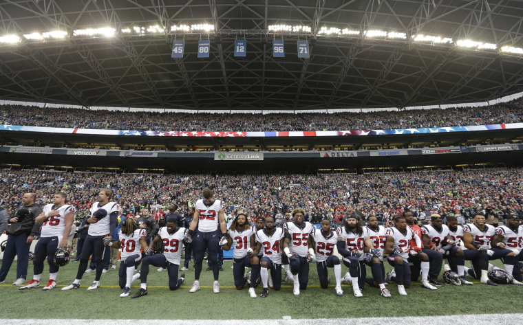 Image: Houston Texans players kneel and stand during the singing of the national anthem before an NFL football game