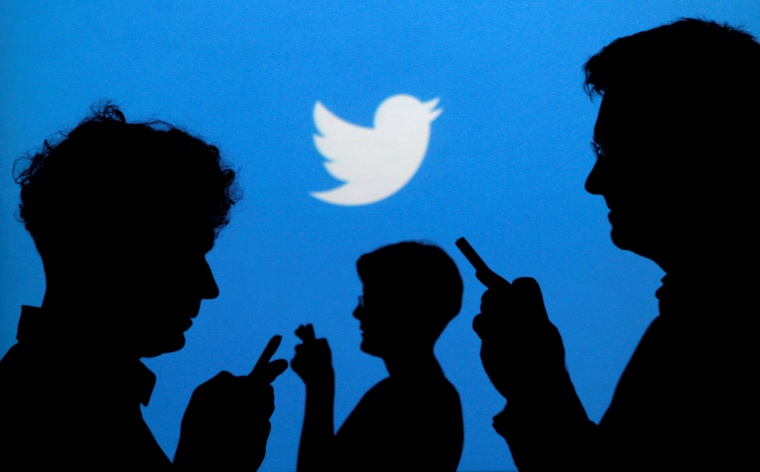 Image: People holds mobile phones in front of a Twitter logo in an illustration