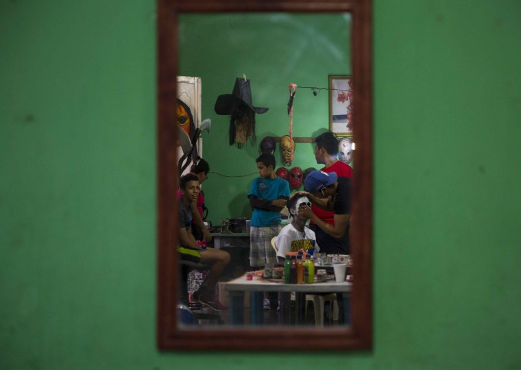 Image: A mirror reflects a man getting his face painted in a workshop during the celebration of the 'Los Aguizotes' holiday in Masaya, Nicaragua on Oct. 27.