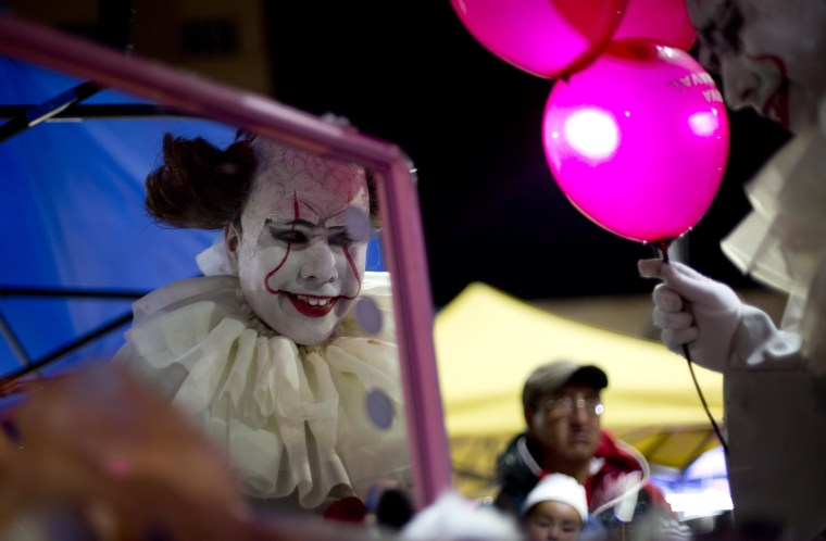 Image: A person dressed in a diabolical clown costume looks in the mirror at the start of the Zombie Walk in La Paz, Bolivia, Oct. 28.