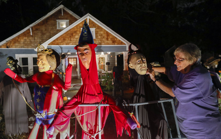 Image: Homeowner Gail Douglas adjusts a likeness of Russian leader Vladimir Putin erected beside one of President Donald Trump and another of Hillary Clinton at her home in Avondale Estates, Georgia on Oct. 28.