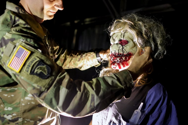 Image: A U.S. soldier serving in the NATO peace keeping mission in Kosovo helps his friend to adjust a mask while taking part in a Halloween party at the U.S. military camp Bondsteel in the village of Sojeve, near the town of Ferizaj, Kosovo on Oct. 29.