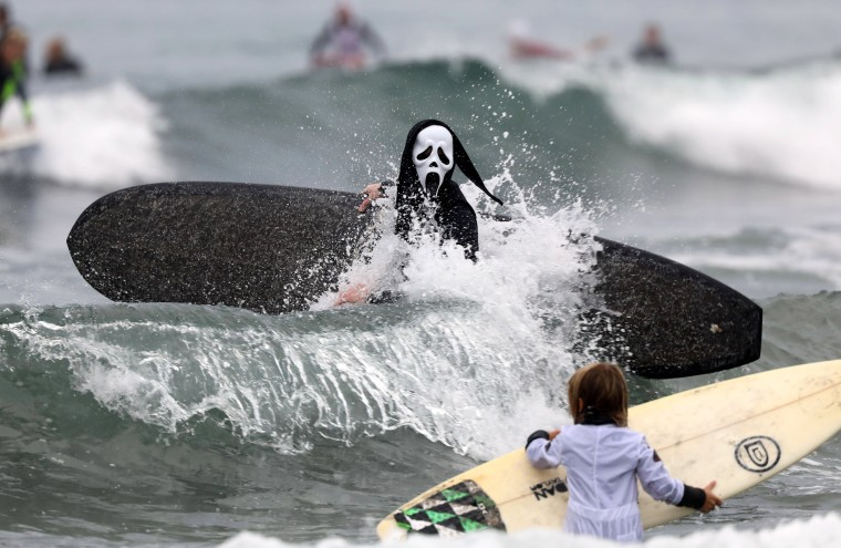 Image: A surfer dressed in a costume from the movie 'Scream' hits the waves during the annual Blackies Halloween Surf Contest in Newport Beach, California, on Oct. 28.