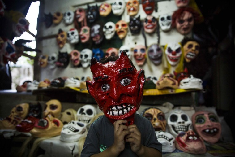 Image: A boy wears a devil's mask as he poses for a photograph in a craft workshop for masks during the celebration of the 'Los Aguizotes' in Masaya, Nicaragua on Oct. 27.