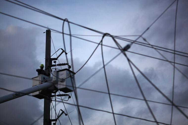 Image: A worker of Puerto Rico's Electric Power Authority (PREPA) repairs part of the electrical grid after Hurricane Maria hit the area in September, in Manati