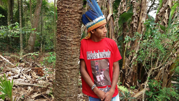 "MC Kunumi poses for a photo in the Krukutu indigenous community, in the city of Sao Paulo, in October 2017. The rapper is wearing a t-shirt stamped with a picture of his appearence in the opening ceremony of Brazil's World Cup in 2014 where he held up a red-and-black poster with the word ""demarcation now."""