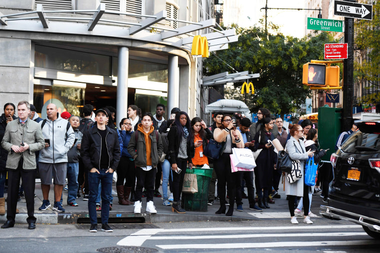 Image: A crowd watches as polioce investigte a shooting in downtown New YOrk