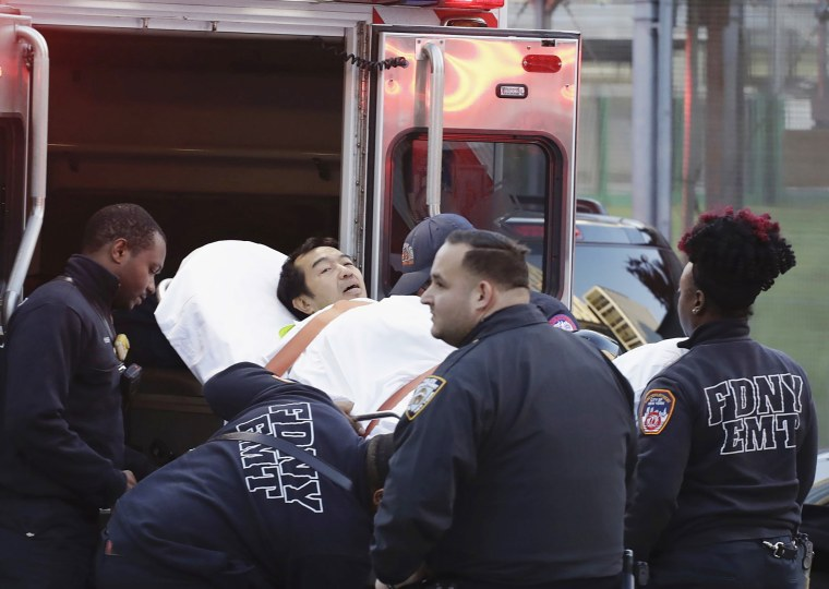 Image: Emergency personnel carry a man into an ambulance