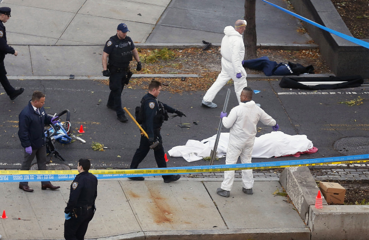 Image: Authorities investigate the scene near a covered body on a bike path