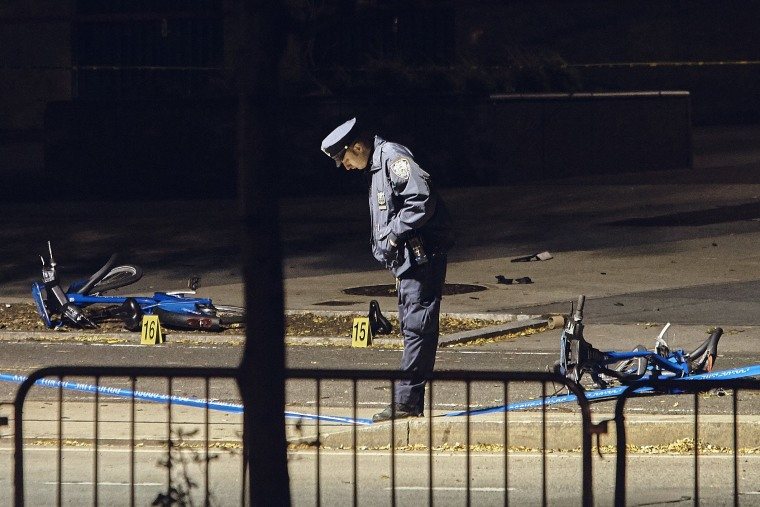 Image: A police officer stands guard on a bike path at the crime scene