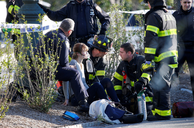 Image: A woman is aided by first responders after sustaining injury on a bike path in lower Manhattan in New York