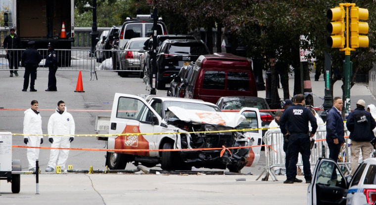 Image: Investigators work at the scene the day after a man in a rented pickup truck mowed down pedestrians and bicyclists
