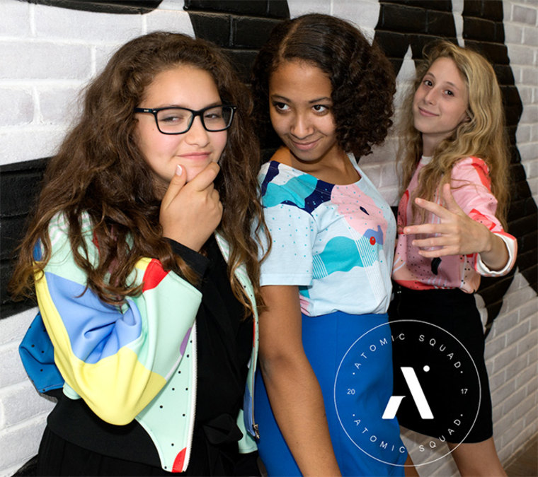 Group of girls hanging out wearing apparel from the ATOMIC by Design clothing line.