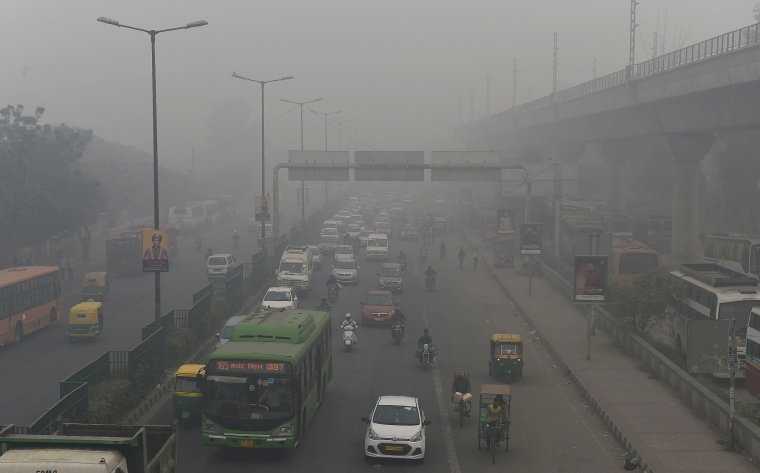 Image: Motorists driving on a busy road as smog covers the capital's skyline in New Delhi