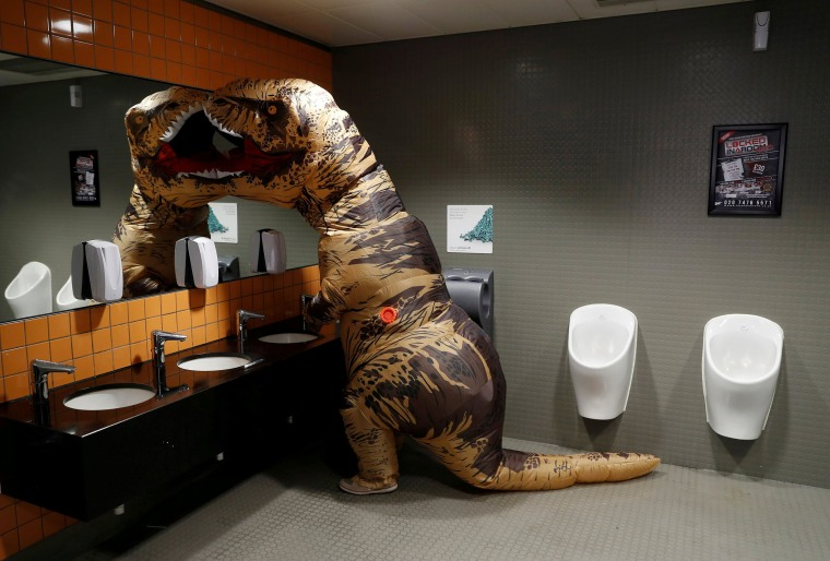 Image: Visitor wearing a T-Rex costume uses the lavatory at the London Comic Con, at the ExCel exhibition centre in east London