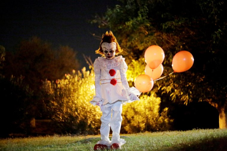 "Image: A boy dressed as Pennywise the Dancing Clown from the movie ""It"" poses for a photo during a Halloween party in Ciudad Juarez"