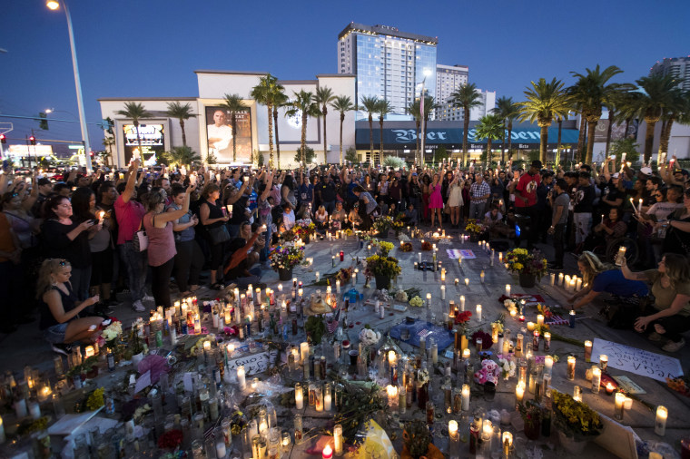 Image: Mourners hold candles during a moment of silence for victims of the Las Vegas shooting