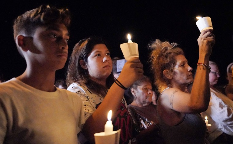 Image: Mourners participate in a candlelight vigil