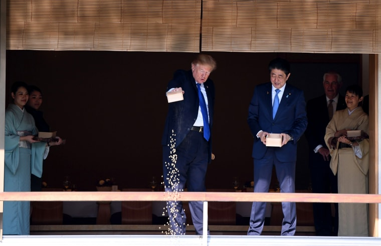 Image: After Prime Minister Abe turned his box of fish food, gently pouring the rest of its contents into the water, President Trump followed suit, slightly more abruptly dumping the remaining food into the pond.