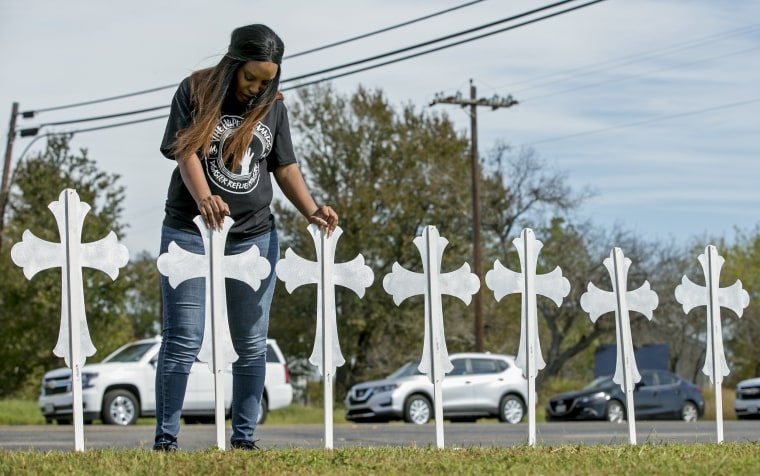 Image: Sheree Rumph of San Antonio prays over two of the 26 crosses erected in memory of the people killed