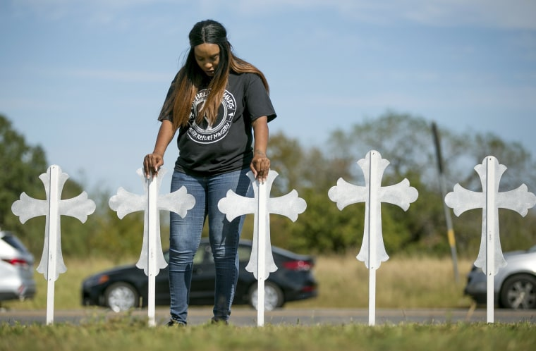 Image: Sheree Rumph of San Antonio prays over two of the 26 crosses