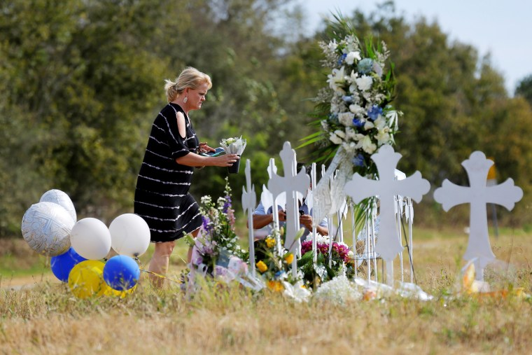 Image: A woman places flowers at a memorial in memory of the victims killed in the shooting at the First Baptist Church of Sutherland in Sutherland Springs