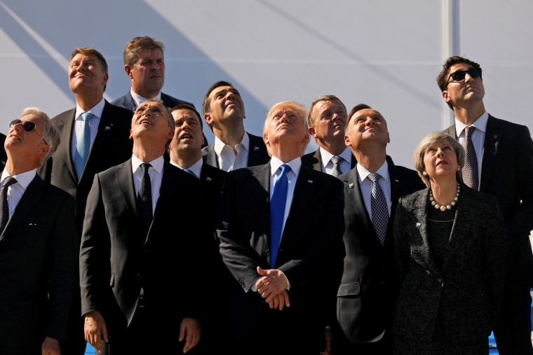 Image: NATO country leaders react during an aerial fly-pass at the new NATO headquarters in Brussels